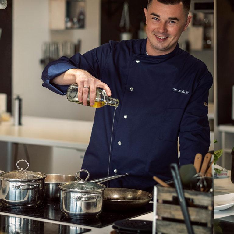 kucharza do wynajęcia Jan Szlachta w kuchni z patelnią i garnkami